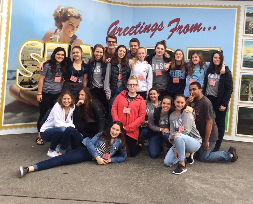 Leadership students pose in front of a sign in Seaside, OR. Image provided by Kira Chan.
