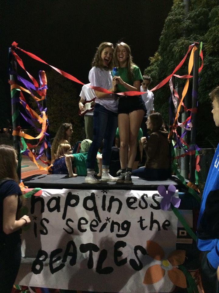 Junior homecoming representatives Tori Tefft (left) and Kayla Nichols (right) get ready to ride out on their homecoming float