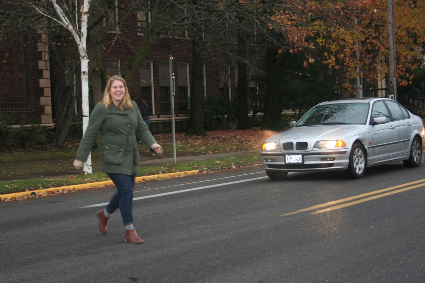 A student crosses the street at the location of the proposed sidewalk