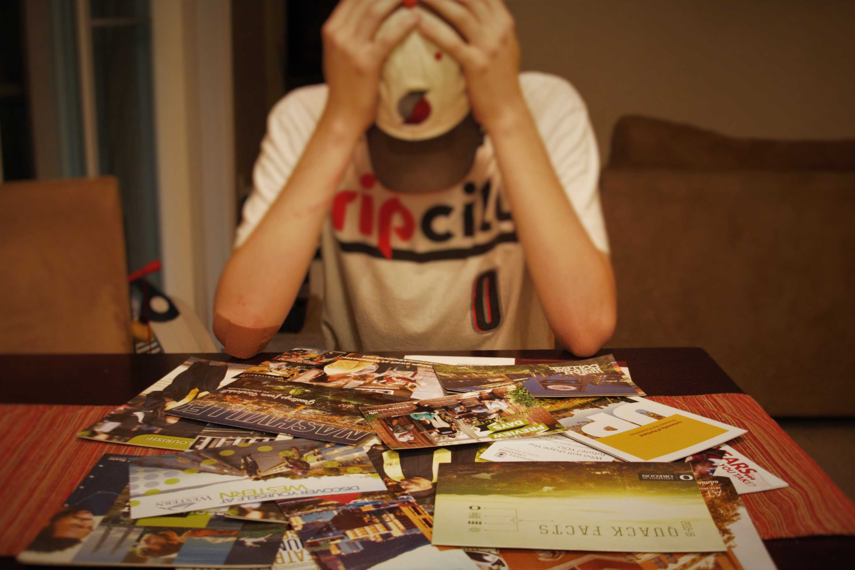 Junior Jackson Latimer stares at a pile of college information packets.