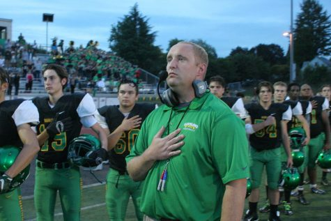 Coach Eric Frasier stands beside his team during the national anthem.
