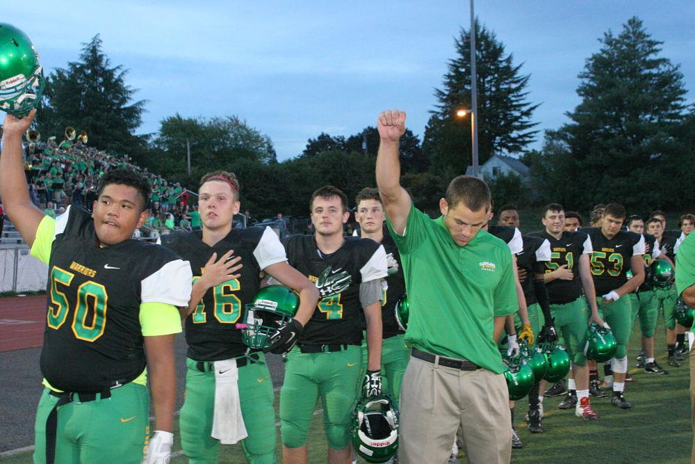 Senior Sione Ofa raises his hand during the national anthem protesting the oppression of people of color. Assistant Coach John Taylor has his hand raised out of a tradition of his, unrelated to any protest.