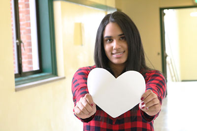 Senior Adriana Hernandez holds out a heart.