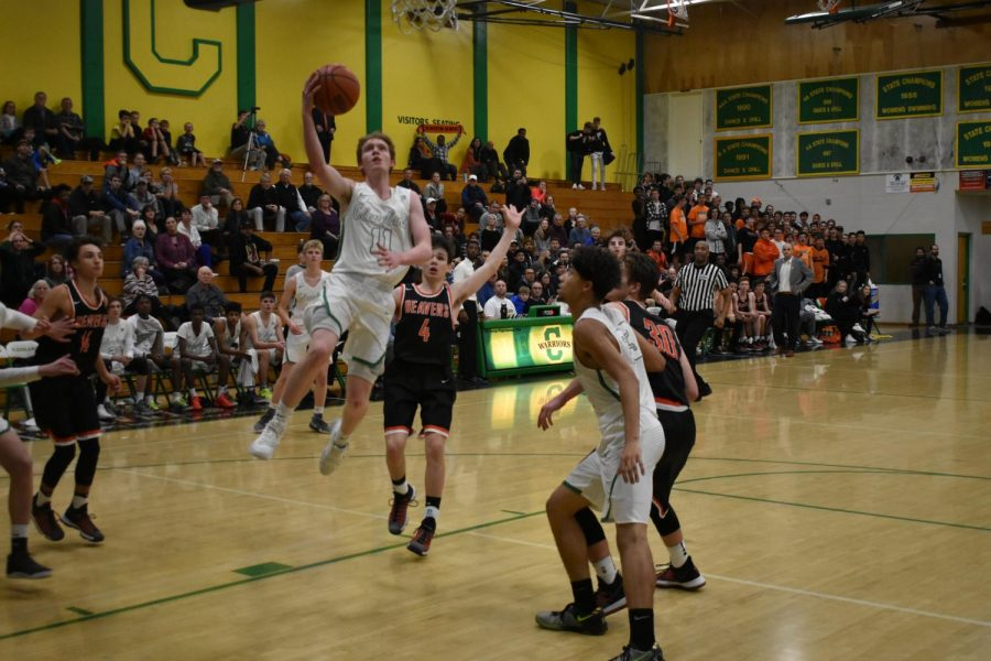Rowan Anderson, who scored a game-high 19 points for the Warriors,  drives to the hoop in the Warriors' season-opening loss to Beaverton Dec. 1.