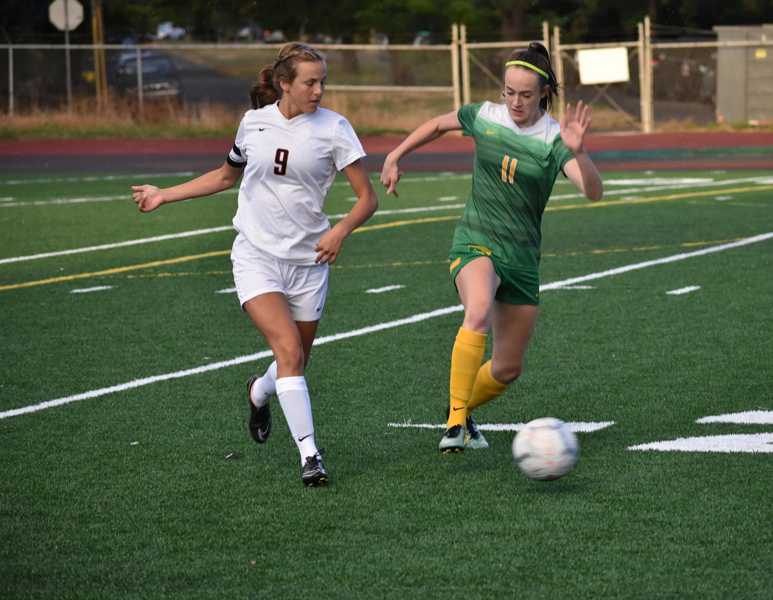 Grace Buchanan, junior, dribbles past defender Katrianne Sinn of Silverton. The Warriors defeated the Foxes 3-0 on Sept. 11 to improve their record to 3-1.