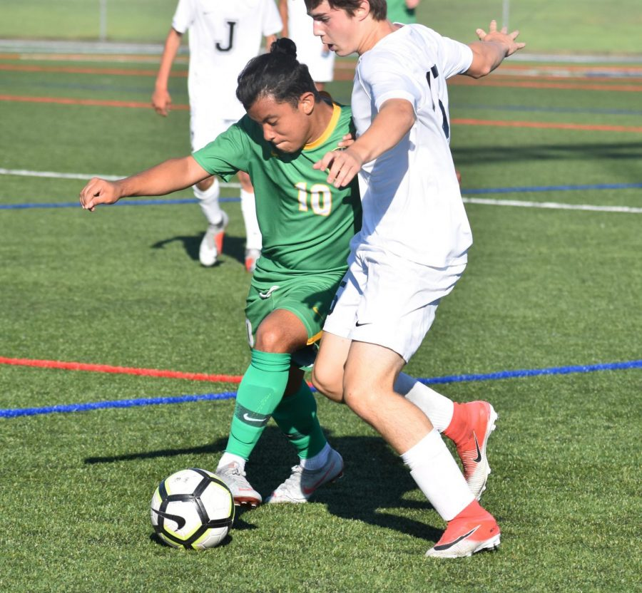 Senior Mario Lemus beats a Jesuit defender in the Warriors' opening varsity soccer game on Aug. 27.  Cleveland lost 4-1.