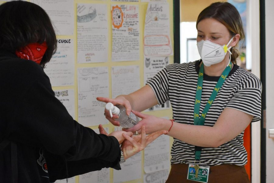 Staff+help+students+stay+safe+by+applying+hand+sanitizer+on+the+first+day+back.+