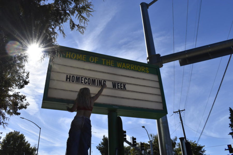 Leadership students hanging up letters in the sign at the front of the school.  HOMECOMING WEEK